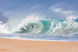 powerful wave exploding on a beach in hawaii