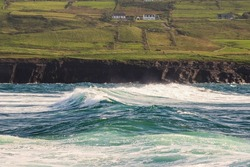 Powerful waves crushing against Cliffs and rough stone coastline of West coast of Ireland. Doolin area. County Clare. Ocean power and rugged Irish coastline. Green fields in the background
