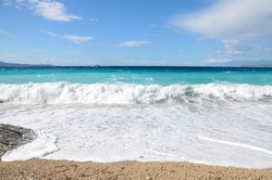 Powerful waves crushing on tropical beach with yellow sand. Waves breaking on the shore at sunset. Coastline. Beautiful sandy beach at summer. Deep blue sea. Wonderful nature. Paradise wild beach.