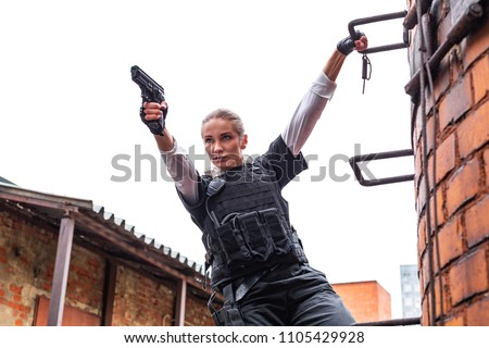 Powerful Woman Holding Gun. War Action Movie Style #1105429928