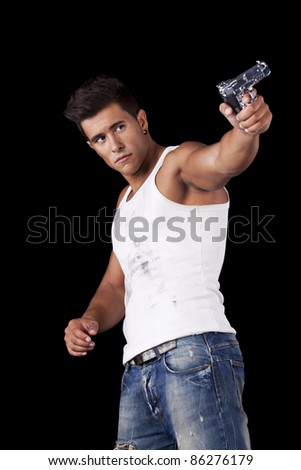 Powerful young man with a gun (isolated on black)