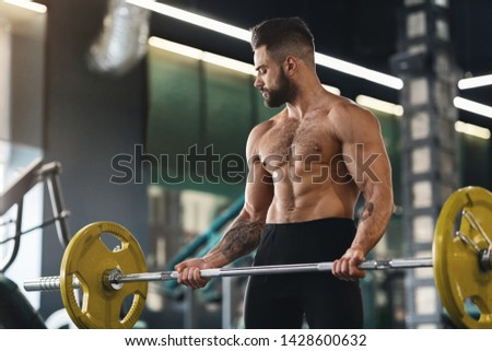 Powerlifter exercising with barbell, preparing for weightlifting competition, empty space