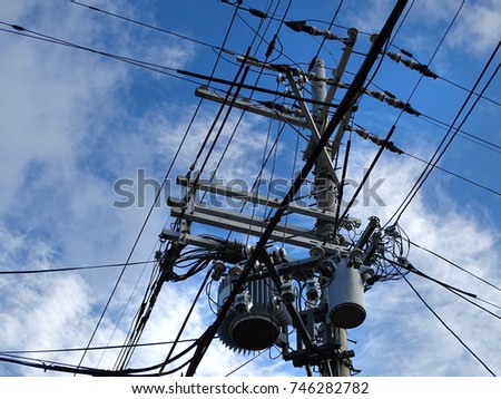 Powerline insulators, connectors, transformers and tangled wires on electrical pole #746282782