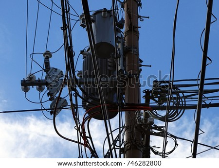Powerline insulators, connectors, transformers and tangled wires on electrical pole #746282800