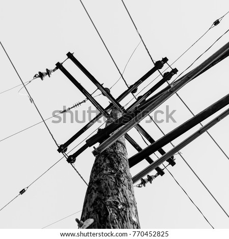Powerlines in monochrome delivering power to people #770452825