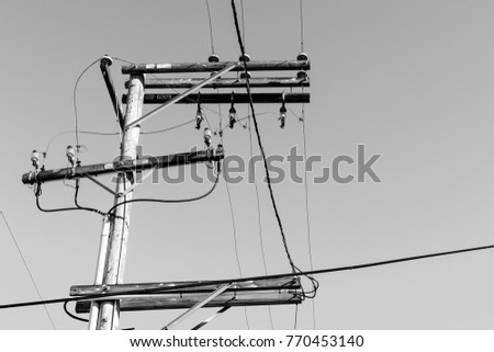 Powerlines in monochrome delivering power to people #770453140