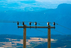 Powerlines on a wooden mast, running though a rural area with mountains in the background.