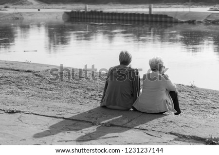 Poznan, Poland - May 1, 2014: Two women sitting on the ground and looking at the Warta river in monochrome colors.  #1231237144