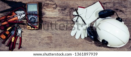 PPE (Personal Protective Equipment) , safety helmet (hard hat) with ear muff attached,Respiratory protection, Pair of leather glove, glasses on old textured wooden plank, Engineering and construction  #1361897939
