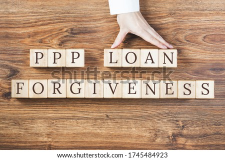 PPP LOAN FORGIVENESS text on wooden blocks on rustic textured background. Female hand holds blocks. Small business Paycheck Protection Program. Banking and finance concept
