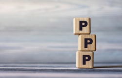 PPP - word on wooden cubes against the background of a light board with beautiful divorces. Business and Technology concept.