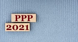 PPP 2021 - words on wooden bars on a gray background with a free space. Business concept