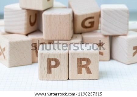PR, Public Relations concept, wooden cube block with letters forming word PR on white gridline notebook, spread of information from organization to the public.