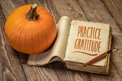 practice gratitude inspirational note - handwriting in a retro journal with a pumpkin against rustic wood, Thanksgiving theme