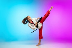 Practice. Karate, taekwondo girl with black belt isolated on gradient background in neon light. Little caucasian model, sport kid training in motion and action. Sport, movement, childhood concept.