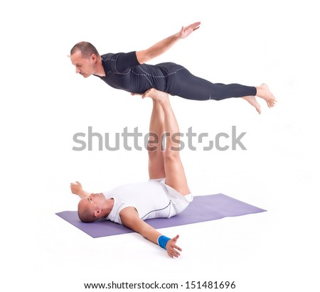 practicing acro yoga exercises in group two man doing