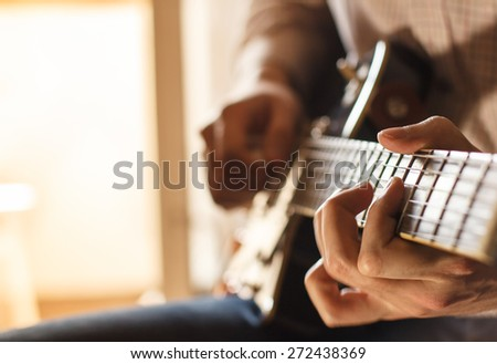 Practicing in playing guitar. Handsome young man playing guitar