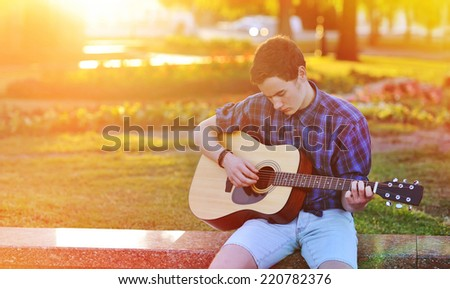 Practicing in playing guitar. Handsome young man playing on acoustic guitar