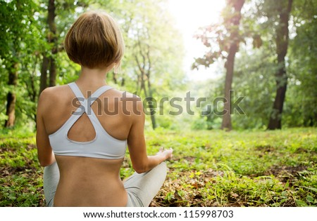 Practicing of yoga outdoors. Young woman In the lotus posture in the sunny forest. Yoga in nature. yoga poses.  Girl from the back.