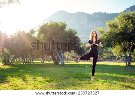 Practicing yoga in the morning, with trees, mountains and sun ray in the background. Attractive young caucasian woman standing in yoga pose on the grass.
