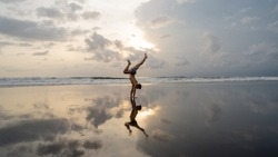 Practicing yoga on the beach at sunset. Handstand balancing pose by fit man on the beach near the ocean at dramatic sunset sky