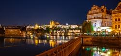 Prague by night. Prague Castle and Charles Bridge reflected in Vltava River. View from Smetana Embankment. Praha, Czech Republic.