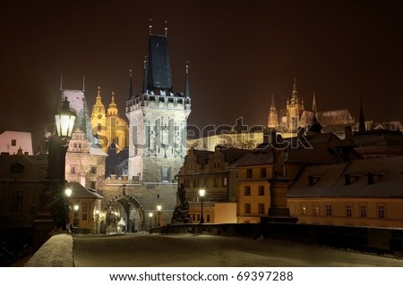 Prague Castle from Charles bridge at night with tower and St. Nicholas church