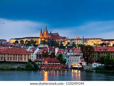 Prague Castle with surrounding buildings across Vltava river in the evening