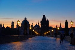 Prague, Charles Bridge early in the morning with unrecognizable tourists and photographers waiting on the bridge for the sunrise