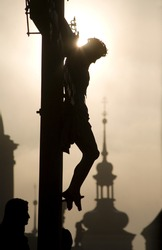 Prague - cross from H. Hilger 1629 on the charles bridge by sunrise - silhouette