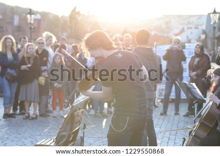 Prague, Czech Republic - April 11, 2015: A musician playing violin on Charles Bridge surrounded by a group of tourists who listen to the performance #1229550868