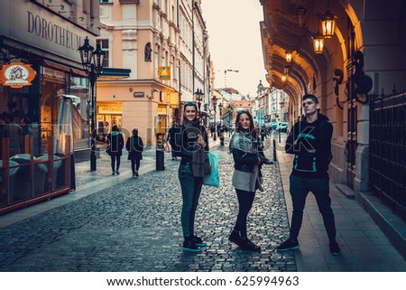Prague, Czech Republic -  APRIL 6, 2017: Three happy young friends having fun on Prague streets. Toned image.