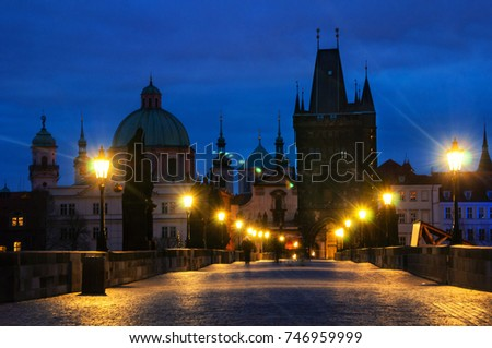 Prague, Czech Republic. Charles bridge in Prague, Czech Republic at night with blurred people. Lens flare, street lamps light and illumination. Early in the morning, dark blue sky #746959999