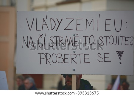 PRAGUE, CZECH REPUBLIC, FEBRUARY 6, 2016: Demonstration against Islam and immigrants in Prague. A man holding a placard with EU governments on whose side you stand to, wake up, Europe, EU