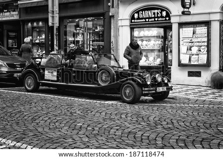 PRAGUE, CZECH REPUBLIC - FEBRUARY 02, 2014: Tour of the city on an old car. Black and white. Stylized film. Prague is the capital and largest city of the Czech Republic.