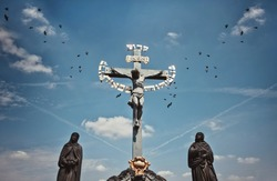 PRAGUE, CZECH REPUBLIC - July 28, 2013:  The statue Crucifix and Calvary on Charles Bridge, many crows in the background