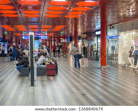 Prague, Czech Republic, March 23, 2019: Travellers people waiting on a train in departure hall and looking on a departure board or shopping in Prague main railway station #1368840674