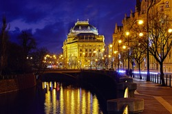 Prague, Czech Republic. Nighttime view to National Theater (Narodni Divadlo) at promenade of river Vltava with bridge, evening illumination and street lamps. Urban autumn urban landscape with trees.