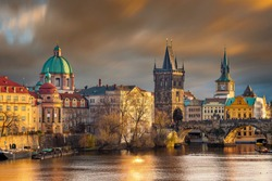Prague, Czech Republic - The world famous Charles Bridge (Karluv most) with St. Francis of Assisi Church and clocktower with beautiful golden sunset lights and moving orange clouds on winter afternoon