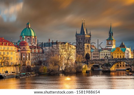 Prague, Czech Republic - The world famous Charles Bridge (Karluv most) with St. Francis of Assisi Church and clocktower with beautiful golden sunset lights and moving orange clouds on winter afternoon Сток-фото ©