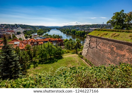 Prague from above with full Vltava river. Amazing colorful summer cityscape with green grass, bushes and trees in the front, view from downtown public park #1246227166