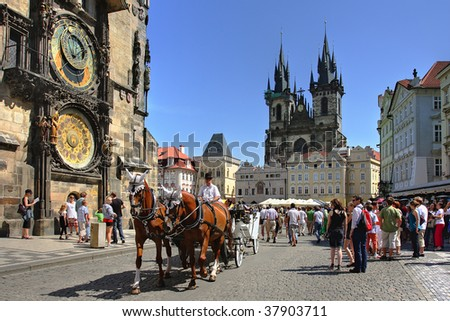 PRAGUE - JULY 17 : Tourist carriage passes by Old Town Square (Stare Mesto) in front of Tyn Church and famous Astronomical Clock july 17, 2009 in Prague, Czech Republic.