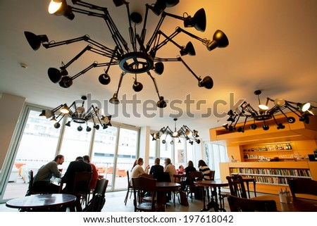 PRAGUE - MAY 16:People sit at the tables in the cafe Museum of Contemporary Art DOX on May 16, 2014 in Czech Republic. The DOX Centre for Contemporary Art and Design opened itself to public in 2008