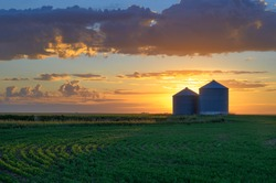 Prairie sunrise on metal grain bins near the city of Moose Jaw, Saskatchewan, Canada