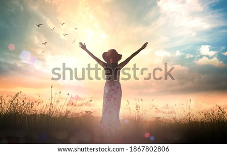 Praise and worship God concept: Silhouette of healthy woman raised hands at meadow sunset background