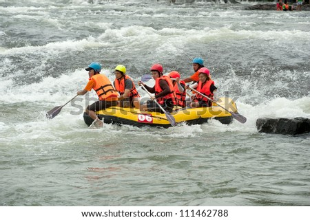 "PRAJINBURI,THAILAND-AUGUST 19 : "" Dragoneye"" team in action at Rafting racing Hinperng's got challenge 2012 on Saiyai river in Khao Yai National park on August 19,2012 in Prajinburi,Thailand."