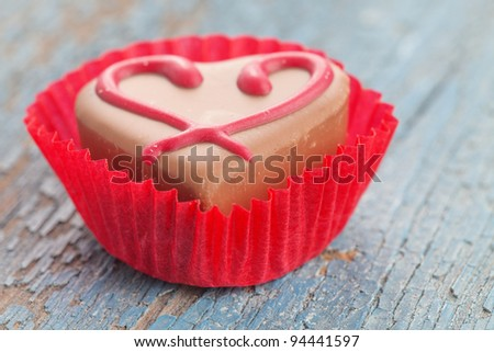 Praline candy in red paper wrap on wooden table