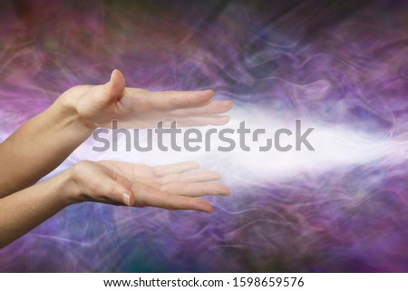 Pranic healer sending focused beam of healing energy -  female parallel hands with a beam of white energy streaming out against a purple energy field background with copy space