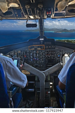 PRASLIN - MAY 21: Air Seychelles pilots in the plane cockpit over tropical island on May 21, 2012 in Seychelles. Air Seychelles operates 160 domestic flights a week throughout the archipelago.