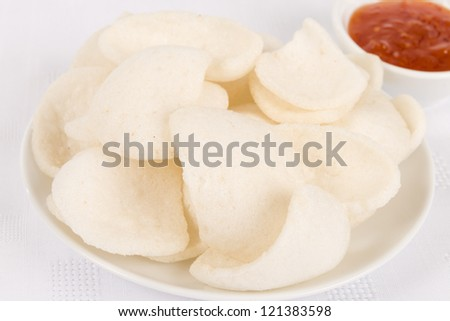 Prawn Crackers - Oriental fried prawn crisps and sweet chilli sauce dip on a white background.
